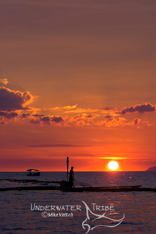 Silhoutte of a young boy standing on a bangka, a local outrigger boat in the Philippines, Anilao, Batangas, Luzon, Philippines, Pacific Ocean