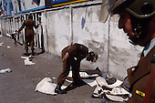 "Santiago, Chile.September 1988..Police remove anti-Pinochet posters from a wall in Santiago after a protest by mothers of missing children in Chile. The mothers, who's children who were arrested for political reasons, were arrested when they began a protest...In 1988, General Augusto Pinochet ordered a plebiscite vote asking Chilean citizens whether he should continue in office. It produced a decisive ""no"" vote and the following year he lost the first presidential election in 19 years. However, under a constitution crafted by his advisors, he remained as army commander until 1998. Pinochet continued to wield enormous power until his arrest in London on human rights charges in October 1998."