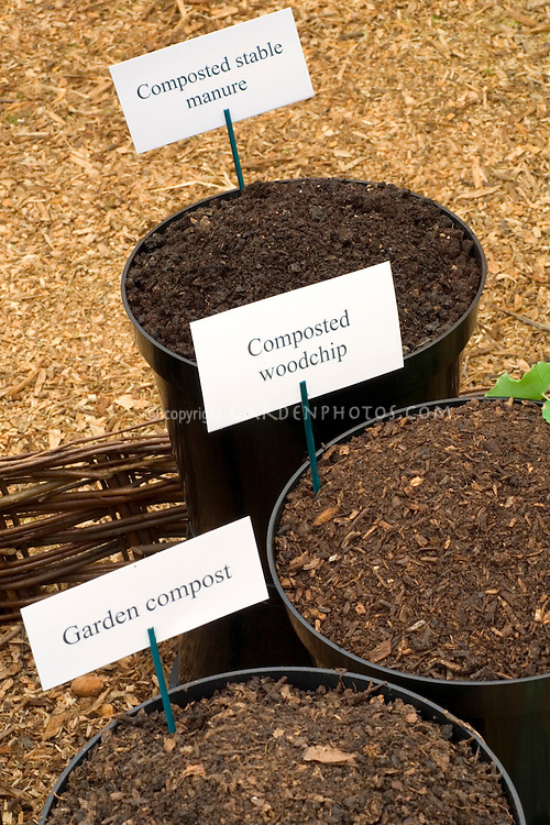 Compost types compared side by side: composted stable manure, composted woodchip, garden compost, in containers with sign labels, for garden use