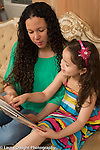 5 year old girl sitting on couch reading picture book with mother