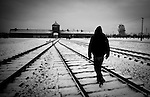 A visitor walks to the main entrance to Auschwitz II-Birkenau concentration camp Sunday Dec 28 2014. Auschwitz concentration camp was a network of German Nazi concentration camps and extermination camps built and operated by the Third Reich in Polish areas annexed by Nazi Germany during World War II, the camp was liberated on January 27, 1945 by Soviet troops. Photo By Eyal Warshavsky