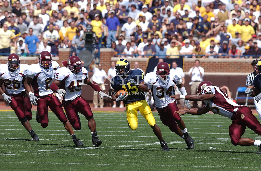 Michigan sophomore Steve Breaston (15) tries to evade the CMU defense during the Wolverine's 45-7 crushing of Central Michigan at Michigan's first game of the season on Saturday, August 30, 2003 in Michigan Stadium in Ann Arbor, Mich. (TONY DING/The Michigan Daily).