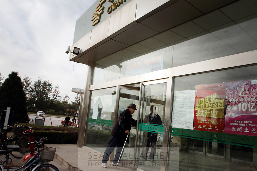 CHINA. Beijing. A man enters the local post office inside the Sun City retirement complex for the elderly. 2010