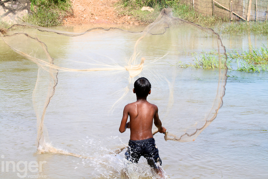 Young boy fishing for his family in Cambodia
