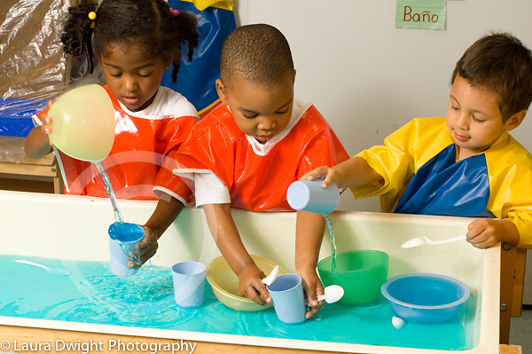 preschool 2-3 year olds group of girl and two boys playing at water table playing separately parallel play
