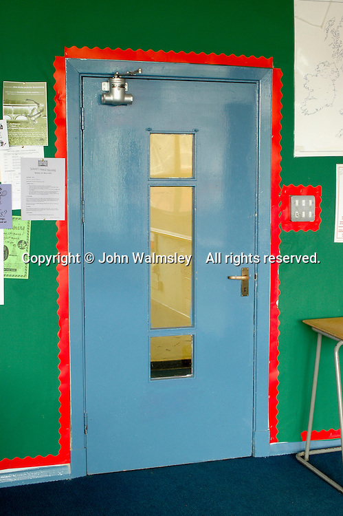 Door with a see-through panel in a school classroom.