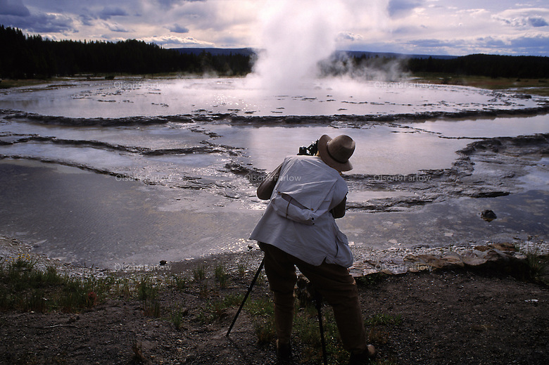 """Tourists takes picture at geyser basins in Yellowstone National Park. Yellowstone is the nations first National Park, it spans three states Yellowstone is the nations first National Park, it spans three states.<br /> The Yellowstone Caldera is the largest volcanic system in North America. It has been termed a """"supervolcano"""" because the caldera was formed by exceptionally large explosive eruptions.<br /> There are 300 geysers in Yellowstone and a total of at least 10,000 geothermal features altogether. Half the geothermal features and two-thirds of the world's geysers are concentrated in Yellowstone."""
