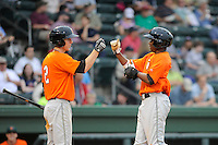 Outfielder Jesus Galindo (33) of the Augusta GreenJackets, right, is congratulated by Matt Duffy (2) after scoring a run in a game against the Greenville Drive on Friday, May 10, 2013, at Fluor Field at the West End in Greenville, South Carolina. (Tom Priddy/Four Seam Images)