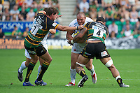 Craig Mitchell of Exeter Chiefs is tackled by Samu Manoa (right) and Tom Wood of Northampton Saints during the Aviva Premiership match between Northampton Saints and Exeter Chiefs at Franklin's Gardens on Sunday 9th September 2012 (Photo by Rob Munro)