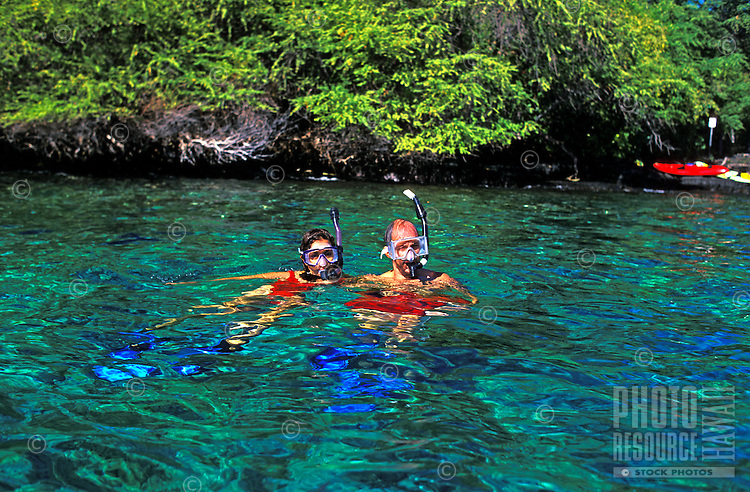A couple wearing snorkel gear tread water in the beautiful clear turquoise water of Kealakekua Bay.