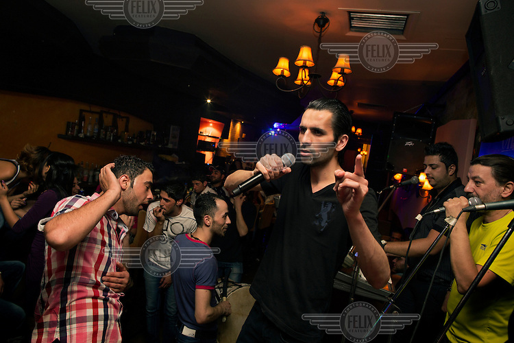 Ismail Otaeashi, 28, performs at the VIP Club, in Damascus, Syria. The club is part of the Cham Palace hotel and Ismail performs twice a night on Thursdays and Saturdays, earning USD 800 per night. His repertoire includes many pro-Bashar al Assad songs.