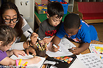 Preschool 4 year olds female teacher working with girl while two boys do writing activity nearby