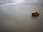 Easter Monday bad weather in Southport England. 9.4.12. An RNLI vehicle drives across the deserted beach.