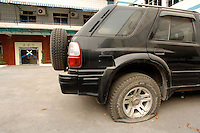 "The bosses car with a flat tyre and covered in dust remains where he left it after fleeing from Dingfu Factory in Houjie Town, Dongguan, China. The sign outside the factory that made shoes for Zara and Nine West amongst others, reads that the ""Dongguan People's Court have closed the factory"". As the economy changes and Chinese labour gets more expensive, factories are closing leaving ghost towns behind them..20 Dec 2007"