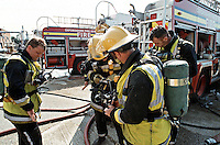 Firefighters in breathing apparatus preparing to enter a large factory fire Oxfordshire UK. This image may only be used to portray the subject in a positive manner..©shoutpictures.com..john@shoutpictures.com