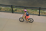Young girl riding bike on sidewalk in Denver, Colorado. .  John offers private photo tours in Denver, Boulder and throughout Colorado. Year-round.