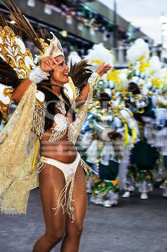 Rio de Janeiro, Brazil. Carnival dancer in white and gold sequinned costume with large gold headdress.