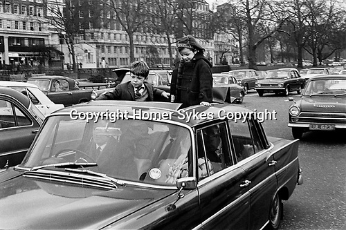 Traffic jam London caused by St Patricks Day Parade 1970s children standing on car seats  stand through sun roof. 70S UK