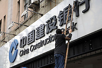 Workers installs a China Construction Bank sign at one of the bank's branches in Shanghai, China..