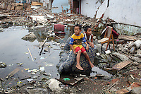 Two young boys sit on a discarded sofa in a flooded district in the northern port area of Jakarta. Almost 40% of Jakarta lies below sea-level leading to flooding in many areas, even during the dry season.
