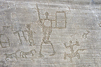 Petroglyph, rock carving, of two warriors with a shield and a man riding a horse. Carved by the ancient Camunni people in the iron age between 1000-1200 BC. Rock no 6, Foppi di Nadro, Riserva Naturale Incisioni Rupestri di Ceto, Cimbergo e Paspardo, Capo di Ponti, Valcamonica (Val Camonica), Lombardy plain, Italy