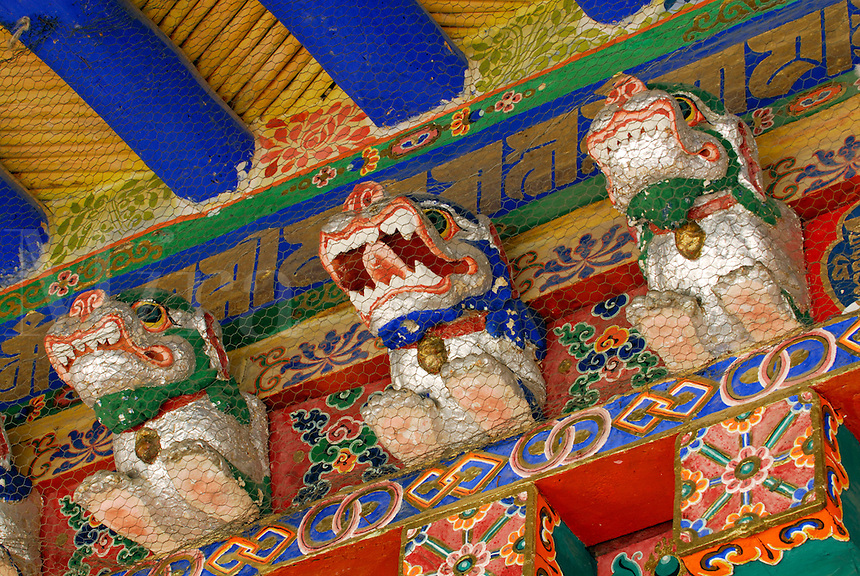 Wood-carved and painted, animal protector deities guard the monastery doorway to prevent entry of evil spirits, Drepung Monastery, Lhasa, Tibet, China..