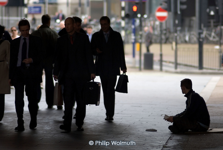 A homeless young man begs from passing commuters in Waterloo, central London.