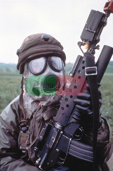 military soldier with large assault rifle dressed in biological warfare suit and gas mask