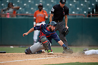 Binghamton Rumble Ponies catcher Dustin Houle (14) attempts to tag T.J. Nichting (out of frame) sliding home safely as umpire Sean Shafer-Markle looks on to make the call during an Eastern League game against the Bowie Baysox on August 21, 2019 at Prince George's Stadium in Bowie, Maryland.  Bowie defeated Binghamton 7-6 in ten innings.  (Mike Janes/Four Seam Images)
