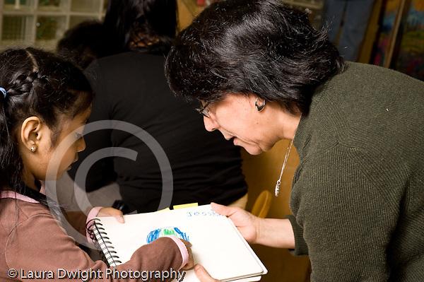 Education preschoool children ages 3-5 female teacher leaning over to hear girl's description of her drawing horizontal