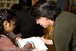 Education preschoool children ages 3-5 female teacher leaning over to hear girl's description of her drawing horizontal