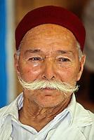 "Tunisia, Sidi Bou Said.  Haj Omar, a Coffee Shop Owner, wearing a Chechia, the traditional Tunisian hat.  The title ""Haj"" indicates that Omar has made the pilgrimage to Mecca."