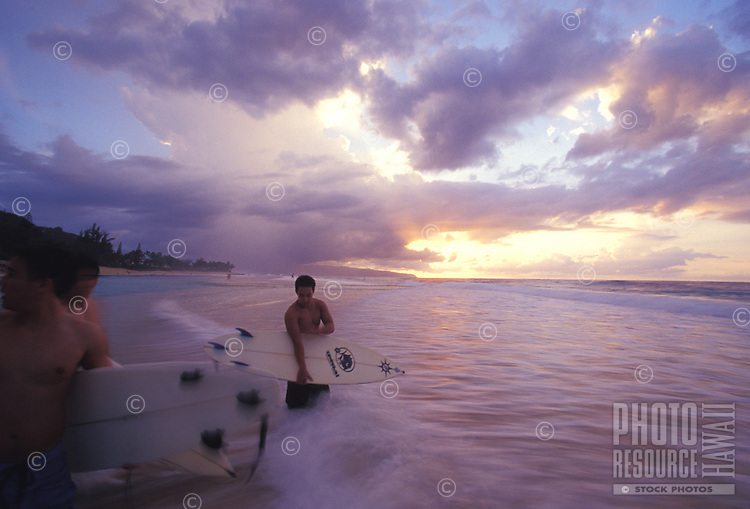 Surfers at sunset holding boards at Ehukai Beach, North Shore of Oahu, Hawaii