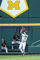 Michigan Wolverines outfielder Christian Bullock (5) makes a catch during Game 1 of the NCAA College World Series against the Texas Tech Red Raiders on June 15, 2019 at TD Ameritrade Park in Omaha, Nebraska. Michigan defeated Texas Tech 5-3. (Andrew Woolley/Four Seam Images)