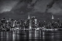 Storm clouds, lingering after a summer thunderstorm and highlighted by the lights of mid-town Manhattan, pass over the skyline of New York City at night.