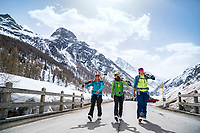 Three women happily carrying their skis into Zinal after ski touring around the Bishorn. Switzerland.