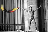 DEUTSCHLAND, 03.10.1990.Berlin - Tiergarten.Feier der deutschen Wiedervereinigung am Reichstag:.Waehrend der feierlichen Ansprachen bestieg ein Mann die Fassade des Reichstages und strippte mit einer Bundesflagge, bis die Polizei ihn herunterholte..Official celebration of the German unification at the Reichstag: During the festive speeches a man climbed the facade and delivered a complete stripshow with a national flag before he was taken down by the police..© Martin Fejer/EST&OST