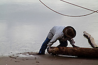 A Brazilian fisherman (jangadeiro) works with a wooden log while pushing the boat on the beach of in Uruaú, Ceará state, northeastern Brazil, 16 March 2004. Jangadeiros, working on a unique wooden raft boat called jangada, keep the tradition of artisan fishing for more than four hundred years. However, being a fisherman on jangada is highly dangerous job. Jangadeiros spend up to several days on high-sea, sailing tens of kilometres far from the coast, with no navigation on board. In the last two decades jangadeiros have been facing up the pressure from motorized vessels which use modern, effective (and environmentally destructive) fishing methods. Every time jangadeiros come back from the sea with less fish.