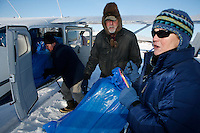 Volunteer pilot Bill Mayer (middle) helps load straw bound for Skwentna into Mike Swallings Cessna 206 at  the Willow airport during the first day of flying straw, musher's dog food bags and people food & gear out to checkpoints south of the Alaska Range.  Saturday Feb. 21,  Iditarod 2009