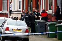 Pictured: David Campbell (also known as David Charmers in grey coat with black sleeves LEFT) is being led away by officers from a house in Raffles Road in Birkenhead, Merseyside, where armed police have placed a containment on a terraced house.<br />