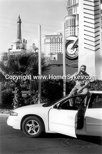 LAS VEGAS NEVADA Ð USA 2001. DOWN TOWN LAS VEGAS, A YOUNG MAN IN SUNGLASSES SITS ON THE ROOF OF HIS CAR SPEAKING INTO A MOBILE TELEPHONE. THE LAS VEGAS EIFFEL TOWER IS IN THE BACKGROUND.