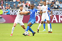 KANSASCITY, KS - JULY 11: Sebastien Cretinoir #21 of Martinique holds off Jonathan Osorio #21 of Canada during a game between Canada and Martinique at Children's Mercy Park on July 11, 2021 in KansasCity, Kansas.