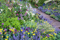 Romantic Victorian style cottage flower gardening with soft pastel colors, stone walkway, pinks, lavender, greens, yellow, blue color themes, lush and beautiful