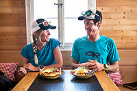 Two people at the Gauli Hut getting ready to eat a classic lunch of Swiss Rösti, during the Berner Haute Route, Switzerland