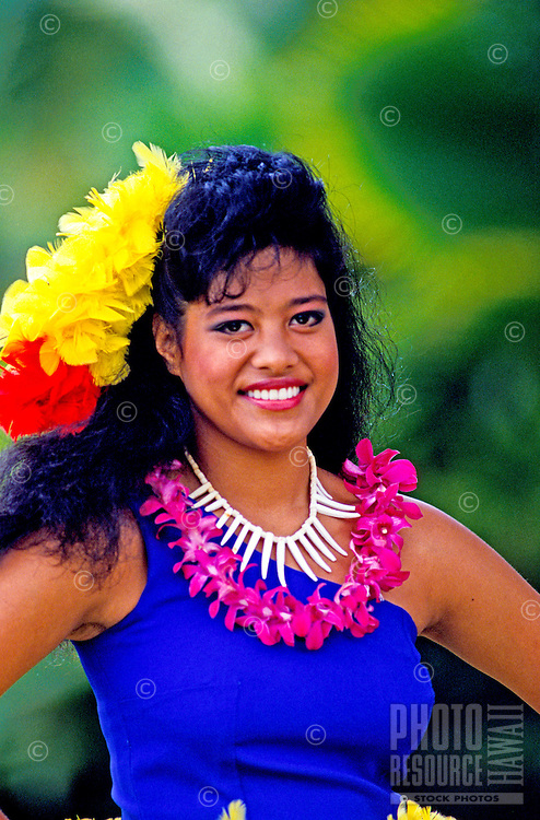 A beautiful young Samoan woman wearing a purple orchid lei, shell necklace and a vibrant yellow and red feather headpiece smiles against a background of muted green foliage.