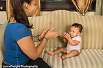 Infant development 9 month old baby girl clapping hands playing with teenage aunt
