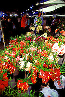 Shoppers stroll through a farmers market in Hilo with a table full of brightly colored anthuriums in the foreground.