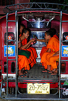 Buddhist monks sitting in a taxi in Chiang Mai city, Thailand, Southeast Asia. They are wearing an orange robed Mahanikai traditional clothe for Thai monks . Buddhist monks must also be treated with respect. Monks cannot touch or be touched by females, or accept anything form the hand of a woman. Rear seats in buses are reserved for monks; other passengers should vacate these seats when necessary.