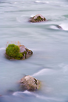 Colorful water flows around boulders in the Chilkoot River, Haines, Alaska