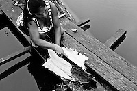 An indigenous woman cuts a river fish in the Amazonian jungle close to Leticia, Colombia, 26 April 2004. Amazonia is the world's largest dense tropical forest area. Since the 16th century the original indigenous people have been virtually pushed away or exterminated. The primal ancient unity between tribes and the jungle ambient has changed into a fight between the urban based civilization and the jungle enviroment. Although new generations of white and mestizo settlers have not become adapted to the wild tropical climate and rough conditions, they keep moving deeper into the virgin forest. The technological expansion causes that Amazonia is changing rapidly.